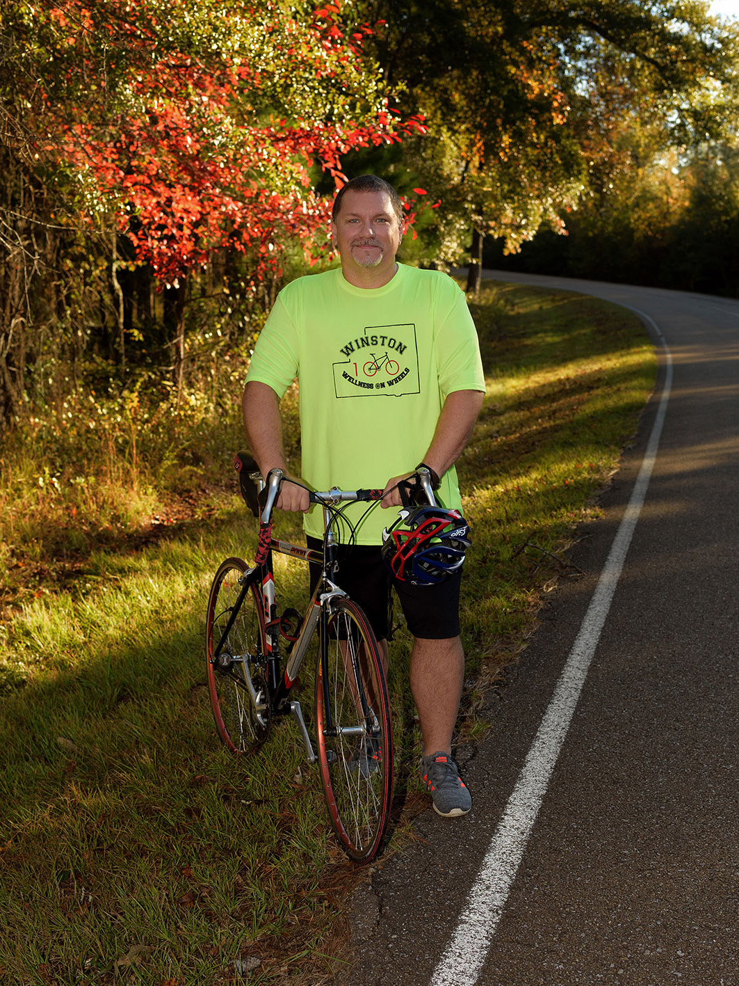 A man wearing a fluorescent green shirt stands holding the handlbars of a black and red bike on the side of a road.