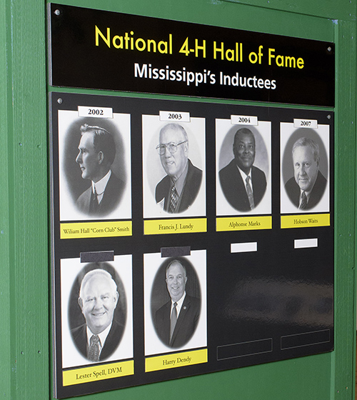 "A green board with the words ""National 4-H Hall of Fame Mississippi's Inductees"" and pictures of six men stands in a building with a Mississippi map in the background."