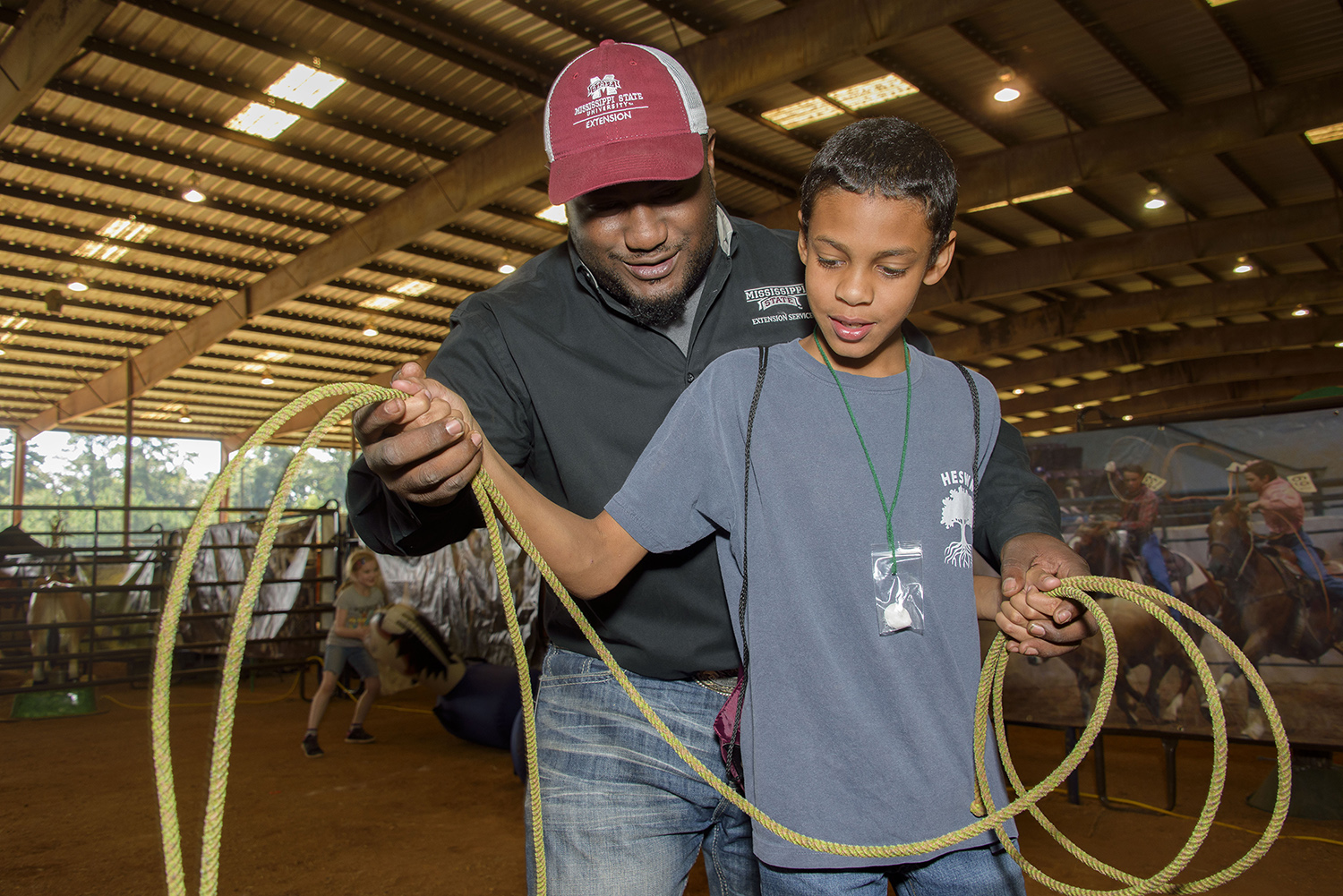 A male African American Extension agent teaches a young African American male FARMtastic visitor how to properly hold a lasso.