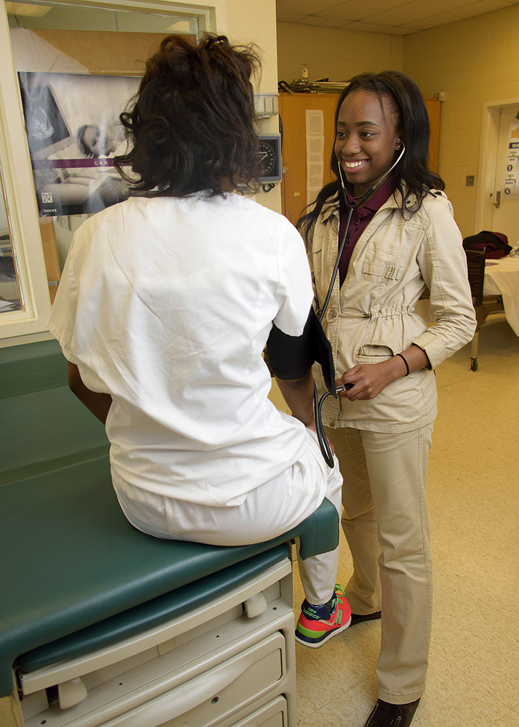 A teenager stands while she checks the blood pressure of another teenager sitting on a physician's table.