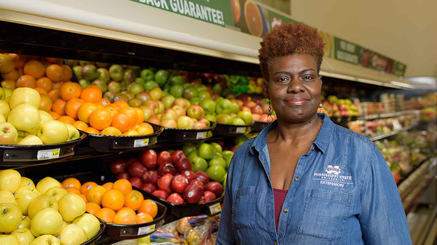 A woman, wearing a denim shirt, smiles in front of a fruit display at a grocery store.