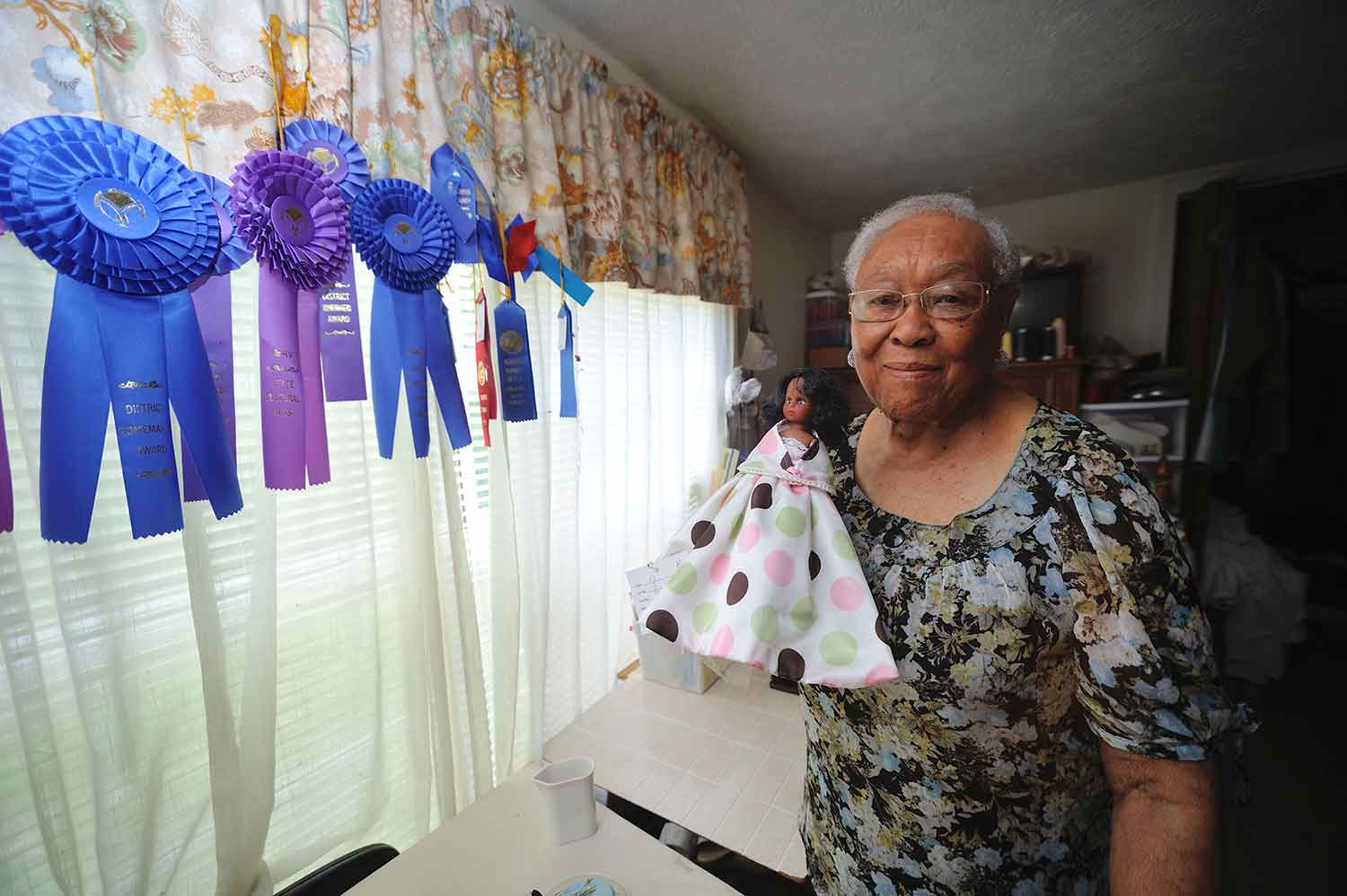 An woman with short grey hair stands to the right of a windowsill with blue and purple ribbons hanging from a multicolored curtain. The woman holds a doll wearing a white dress with light green, light pink, and dark brown polka dots.