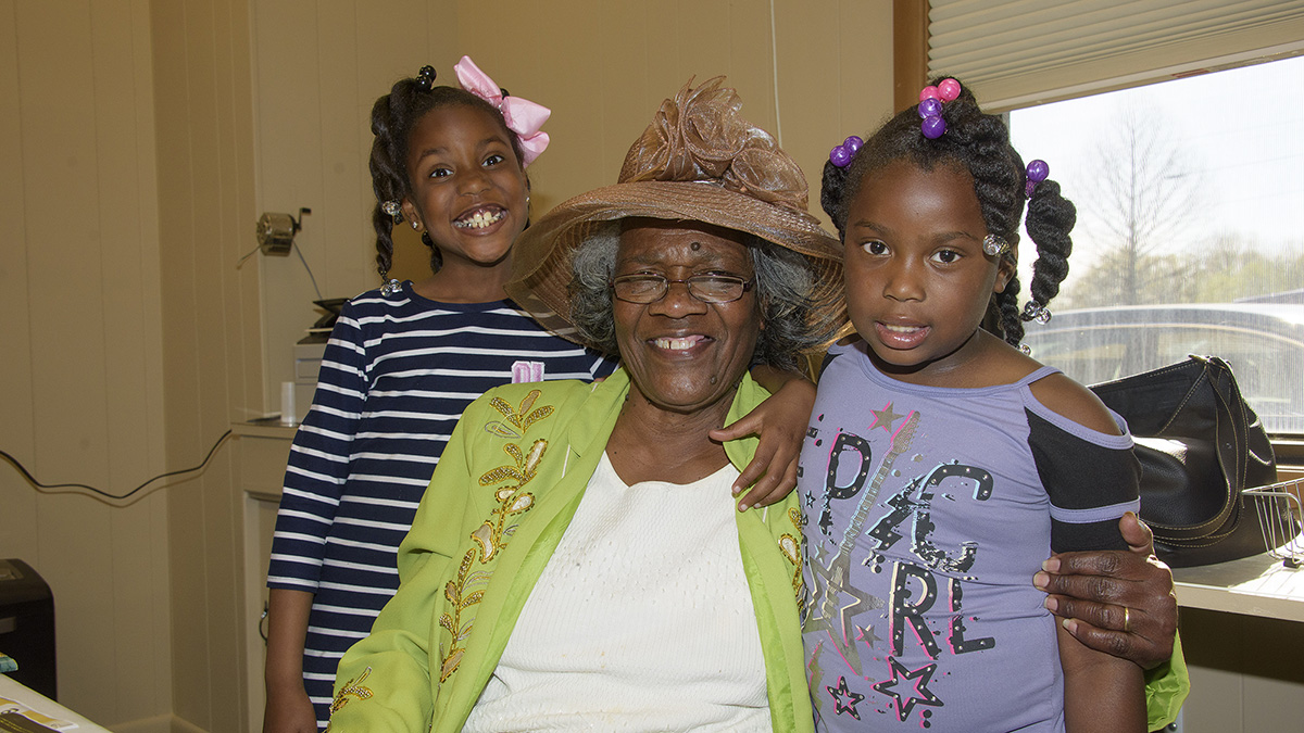 A young girl wearing a purple shirt, a young girl wearing a striped shirt, and an older woman wearing a large brown hat and a bright green jacket smile at the camera.