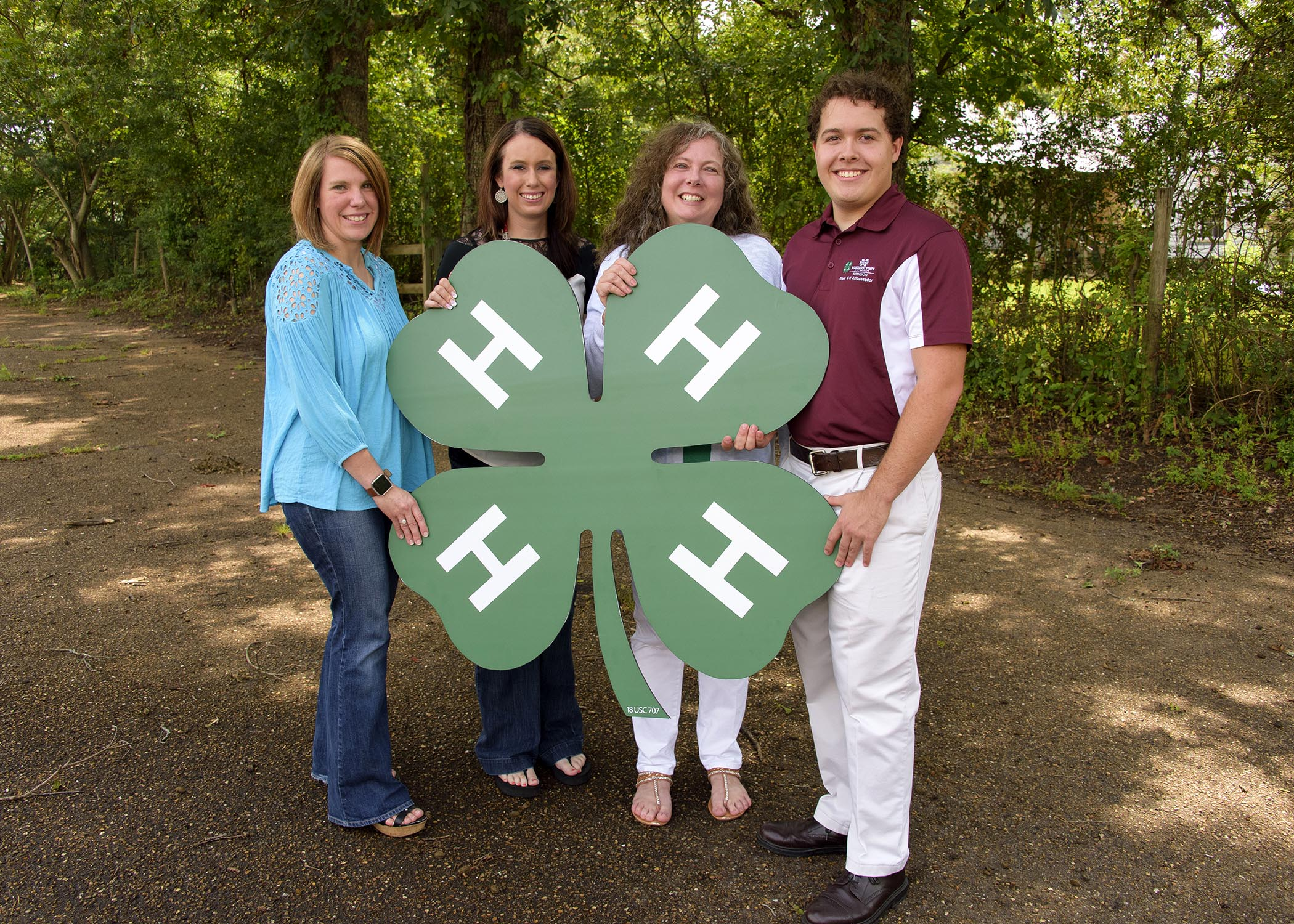 Three females and one male smile as they hold a wooden cutout of the 4-H logo.
