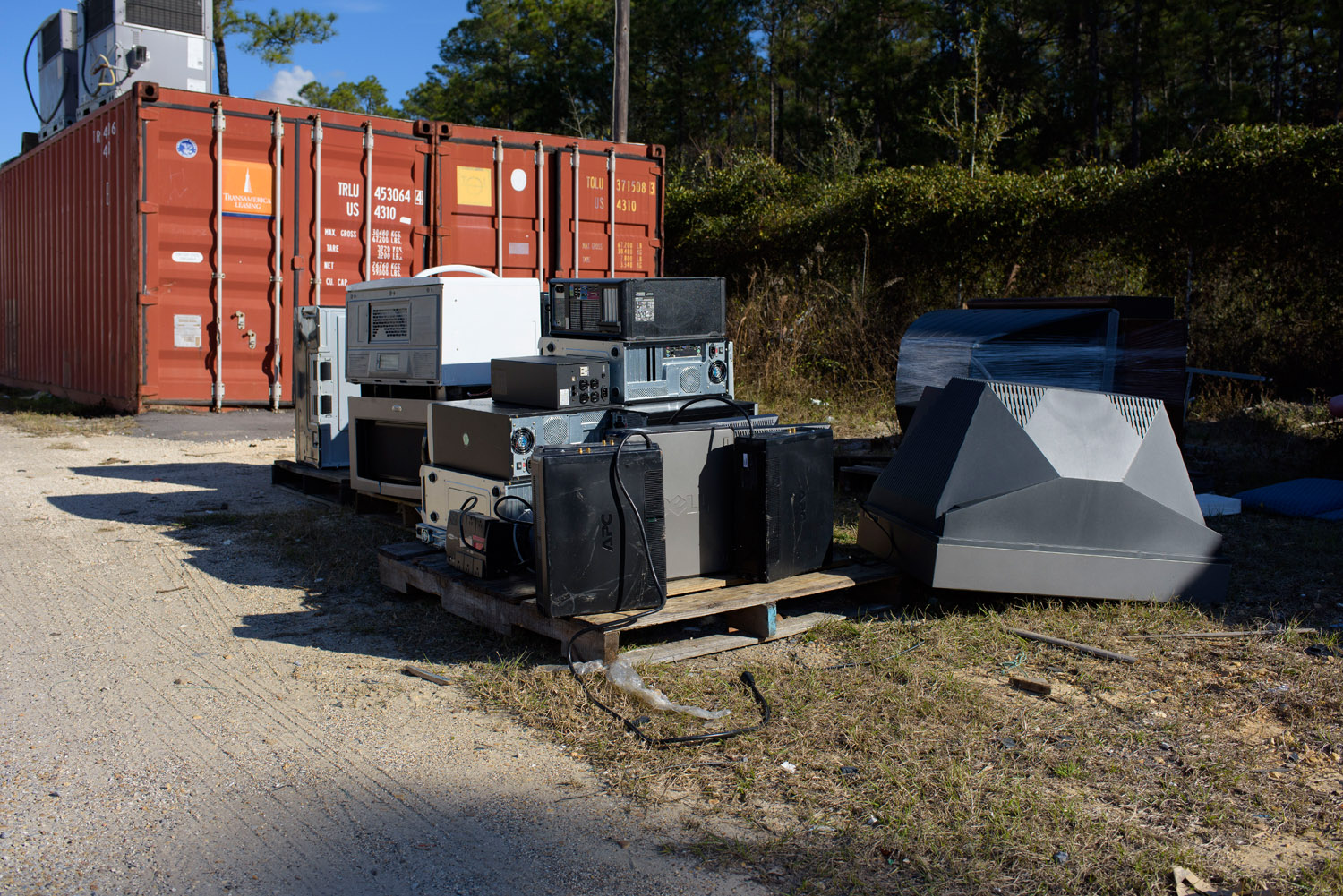 In front of a railroad car on the sand, an overturned tube television, right, shines beside a pallet loaded with old VCRs, CPUs, and microwaves.