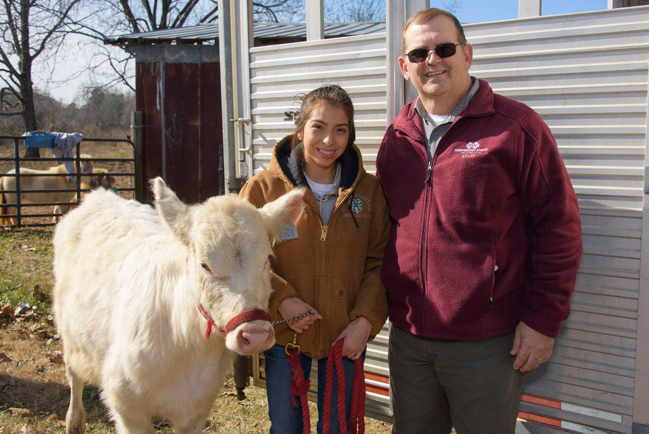 A female teen in a brown 4-H jacket, and jeans stands smiling between a man wearing sunglasses and a maroon pullover and a white cow.
