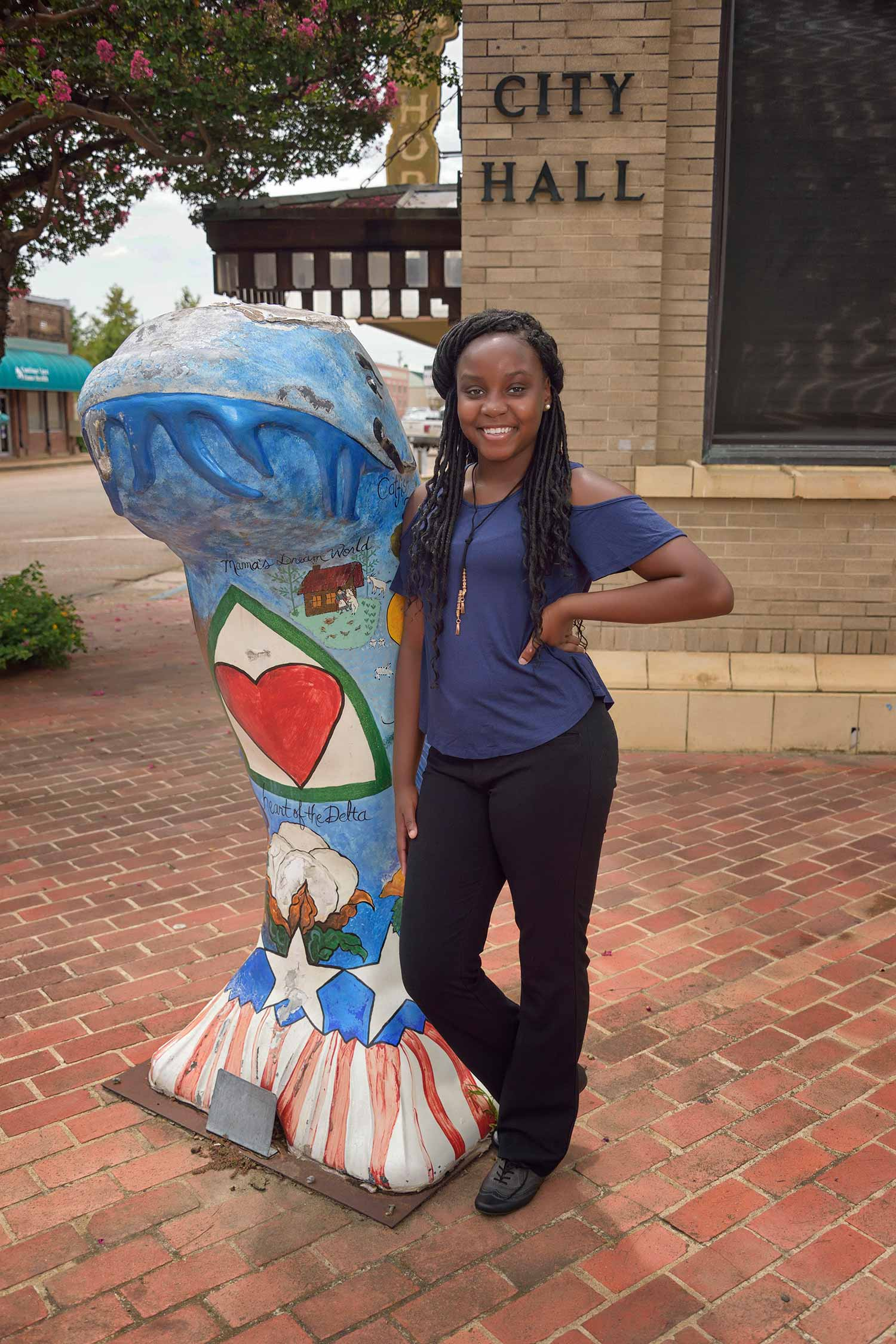 "A teen girl with a blue shirt and black pants stands in front of a building labeled ""City Hall"" and to the right of a statue of a catfish, blue on top with red and white strips on the bottom fin."