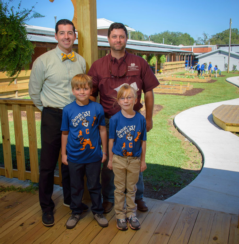 "Two men, one on the left in a white & blue striped polo and one on the right with a maroon polo, stand behind a male and female child, both blonde and wearing T-shirts with ""Central is Gr-r-reat!"" and a tiger printed on them. They all stand on a wooden patio in front of a small farm site."