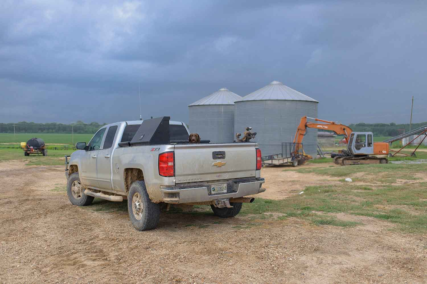 A silver truck with a brown dog peeking its head out of the bed is parked on a dirt lot with farms in the background. Two large, round, metal buildings are just past the truck, and an orange bulldozer is parked in front of one of the metal buildings