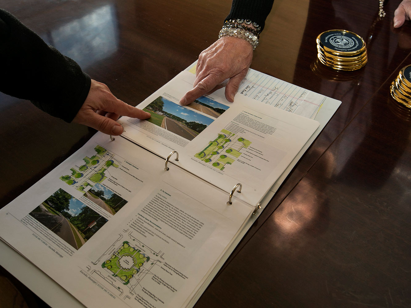 A binder with plans for the city is open on a table, and tow hands are pointing at a picture of a road in the binder.