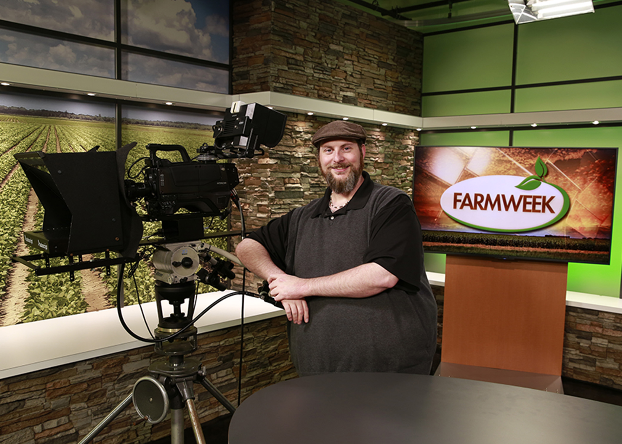Bearded man in hat on Farmweek TV studio set.