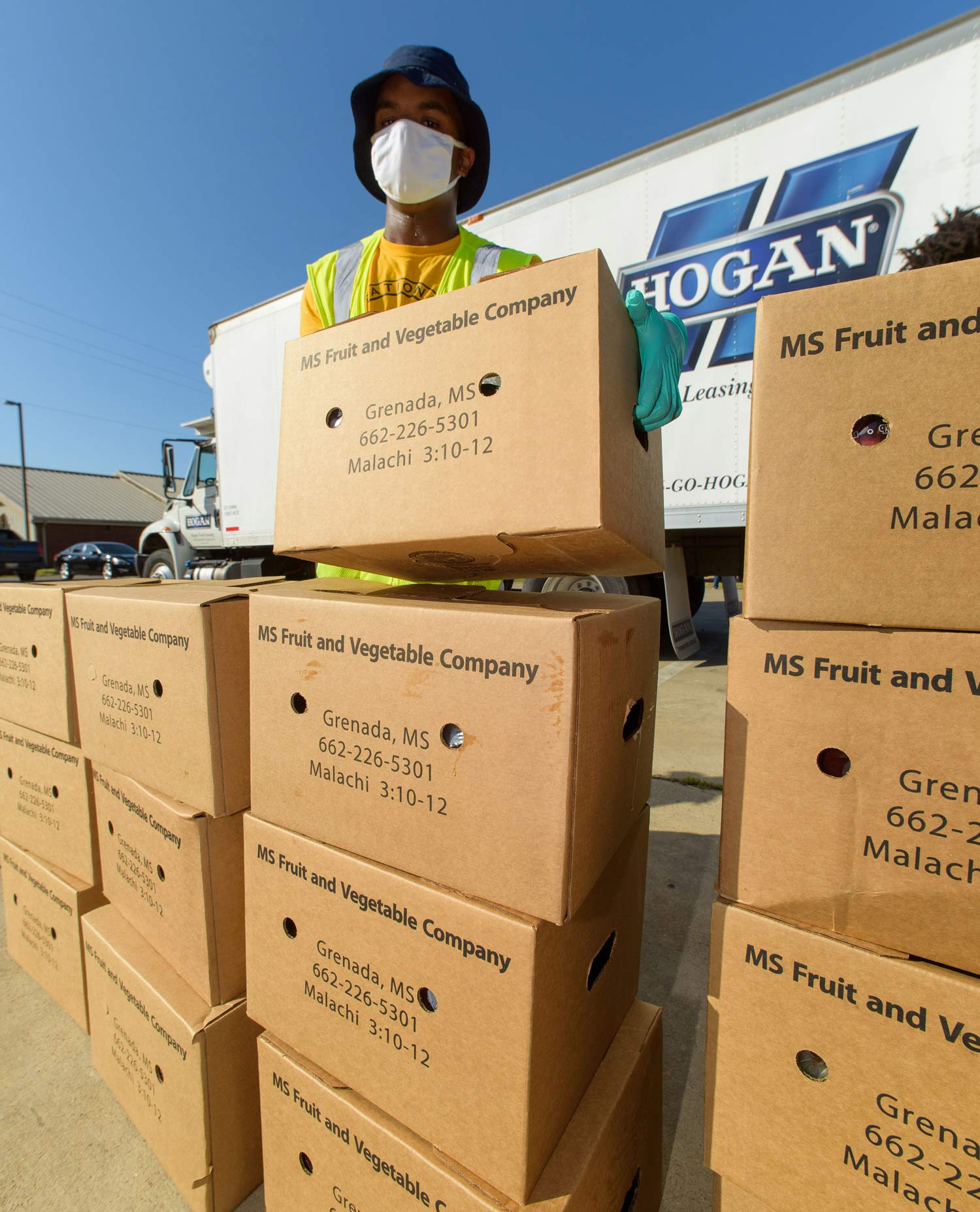 "A man wearing a mask stands behind a tall stack of cardboard boxes labeled ""MS Fruit and Vegetable Company."""