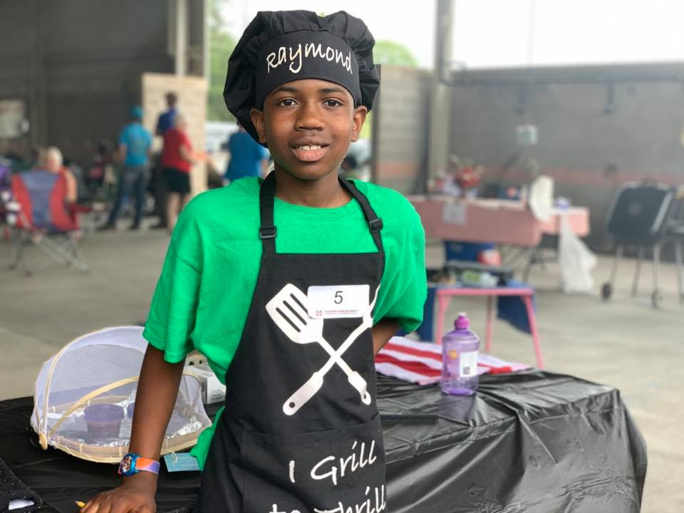 "A young boy wearing a green shirt, black apron, and black chef's hat that says ""Raymond."""