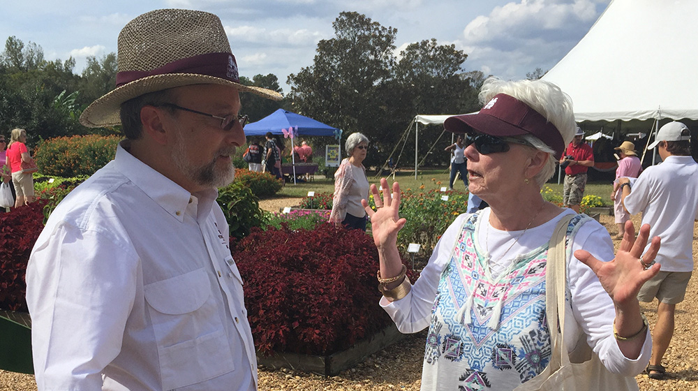 Extension specialist talks with a woman in a raised bed flower garden during an outdoor gardening seminar