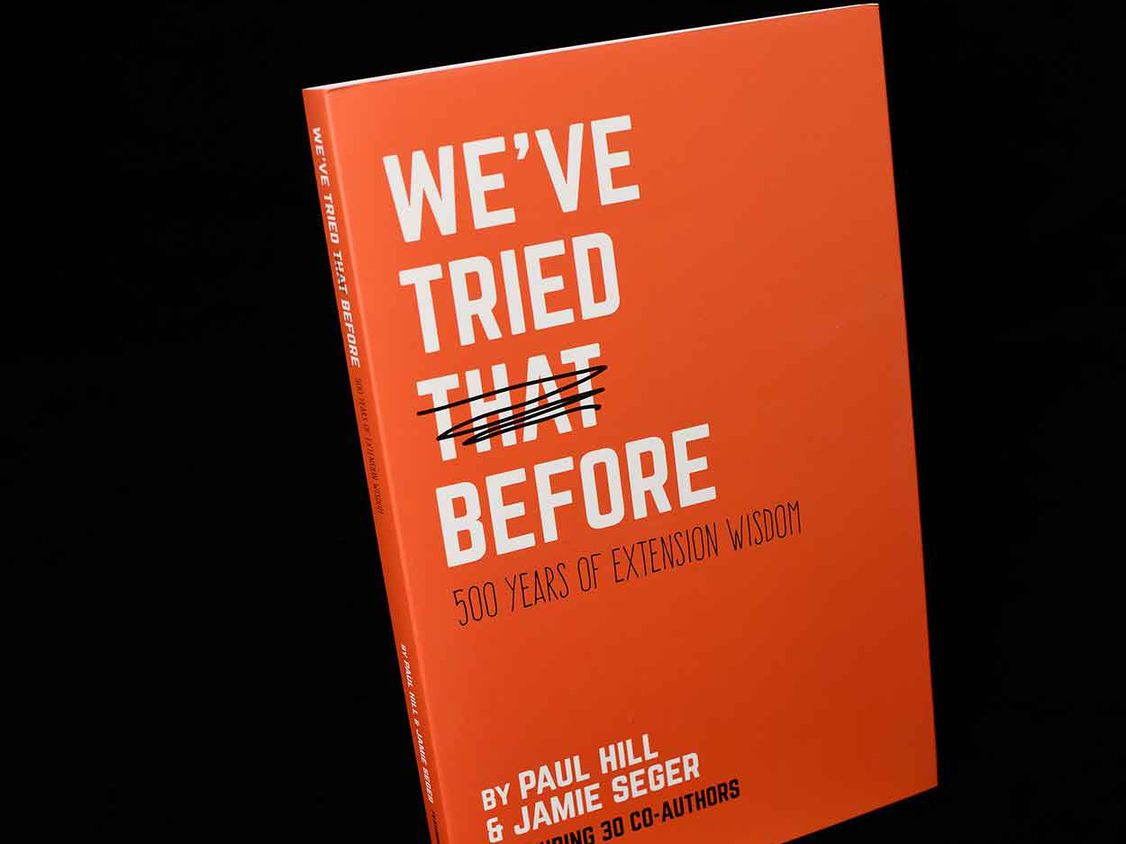 "An orange book lies on a black background; the cover of the book, in white, reads, ""We've Tried That Before: 500 Years of Extension Wisdom."""