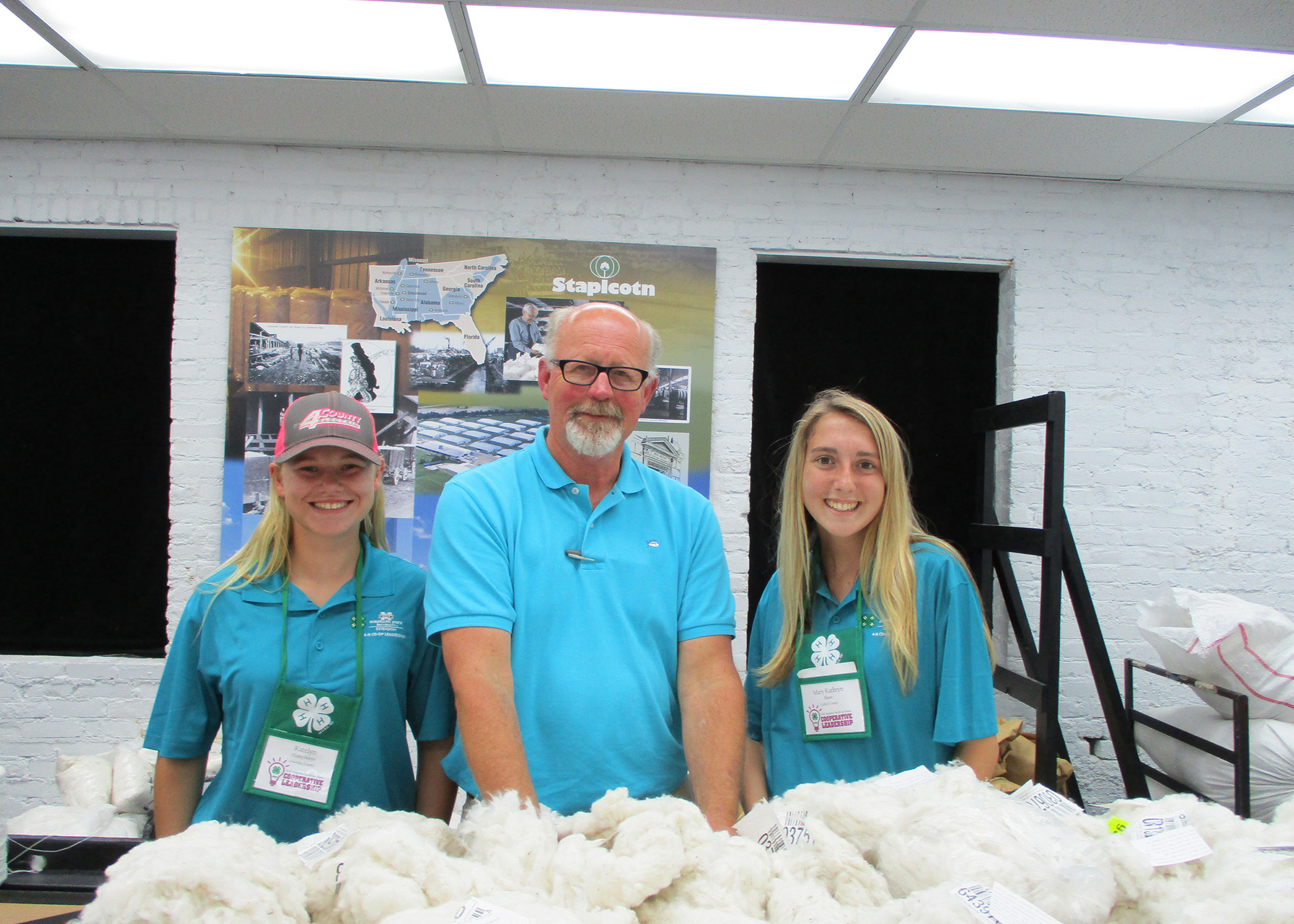 Two blonde haired girls and a middle age man all wearing blue shirts pose next to a table with cotton on it.