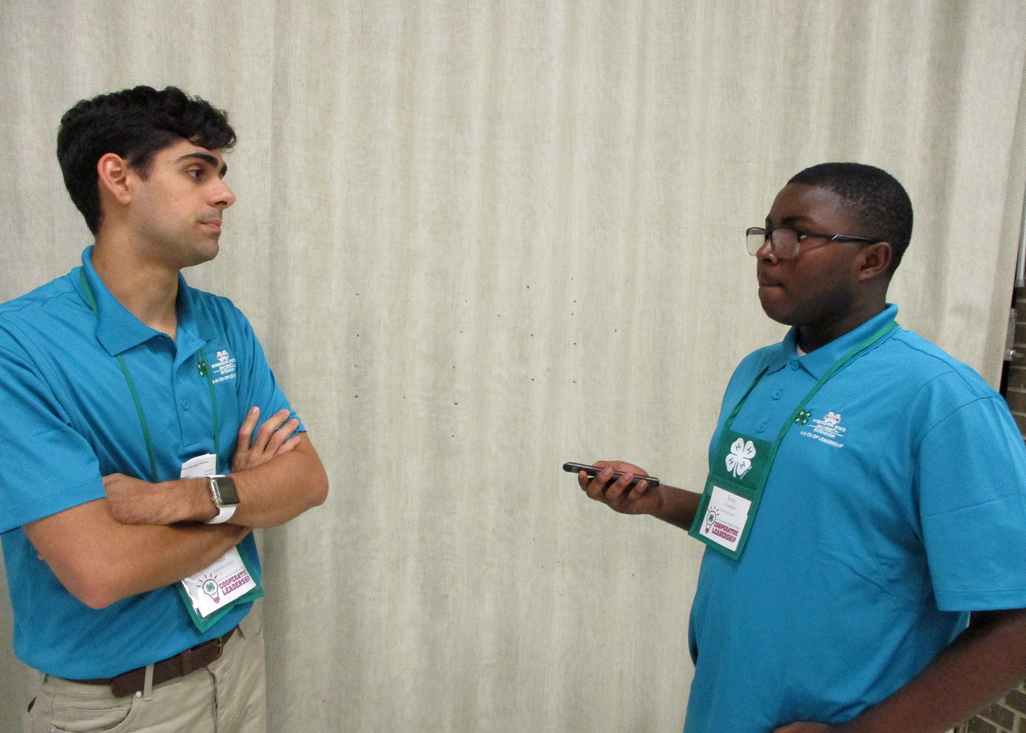Two young men wearing blue shirts talking to each other