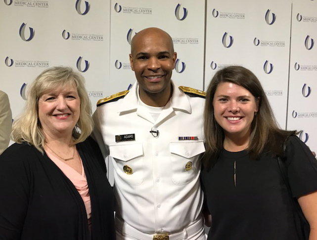 An African-American man wearing a white U.S. military uniform stands smiling. A blonde woman in a black blazer stands on the left, smiling, and a brunette in a black blouse stands on the left.