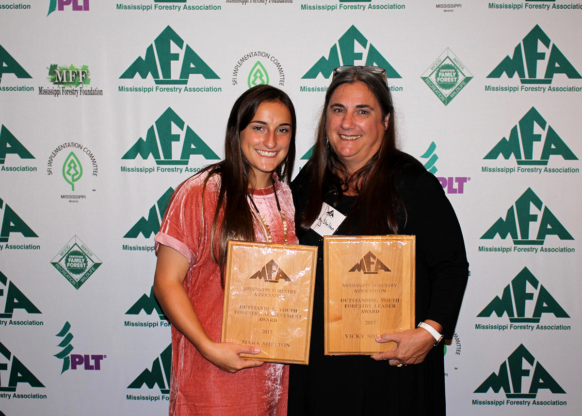 Two women stand while holding award plaques at the Mississippi Forestry Association annual meeting.