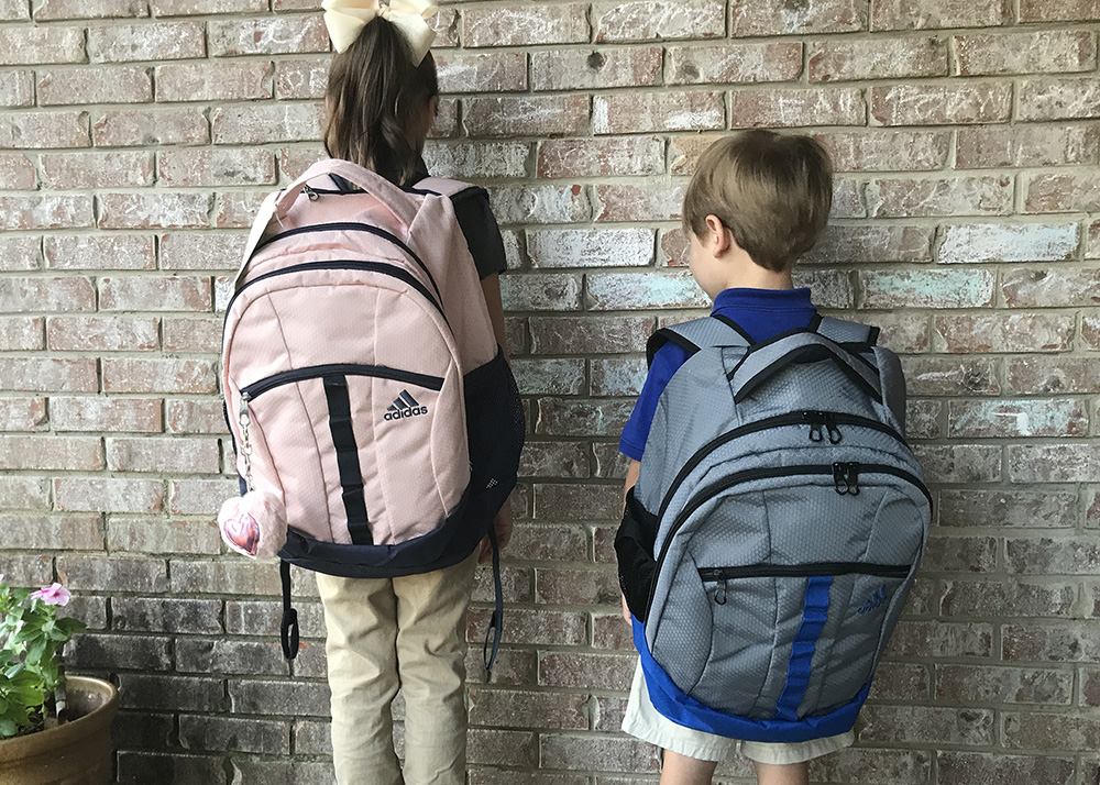 Two children wear backpacks to demonstrate the proper fit.