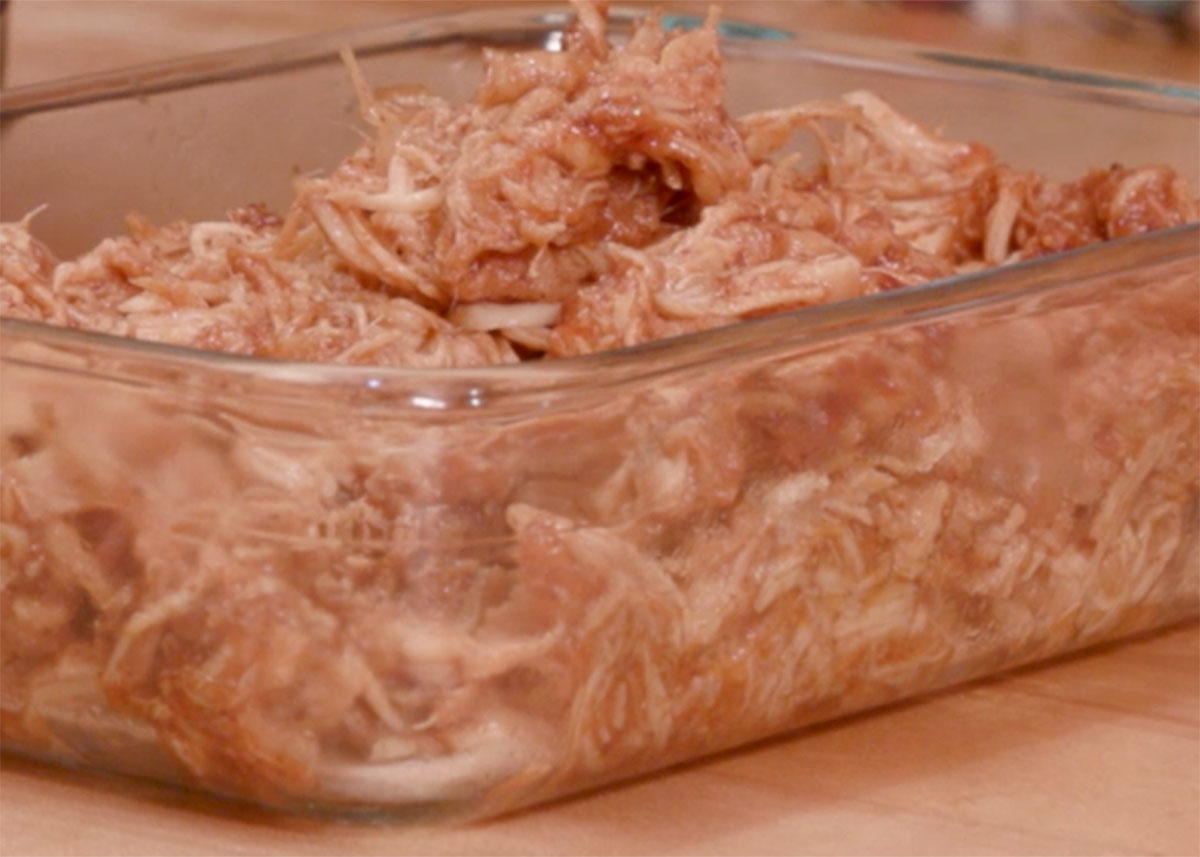 Shredded Chicken Breasts Coated In Barbecue Sauce A Rectangular Clear Glass Container