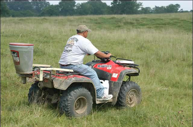 A man riding a four wheeler, in a pasture, with a spreader attached for applying granular fire ant bait.