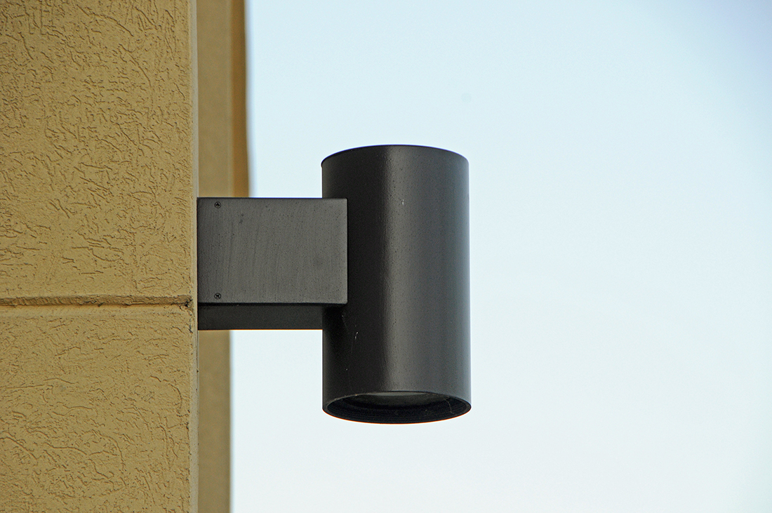 A dark metal exterior light mounted on the side of a beige building.