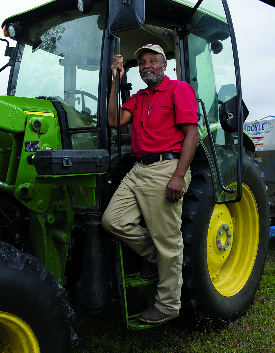 A man standing in the door of a tractor.