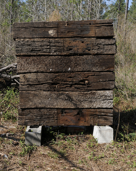 Six railroad crossties stacked on two cinder blocks in the woods.