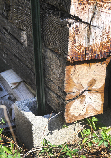 Closeup of the bottom of a backstop, showing the fence T-post through the center of a cinderblock opening.