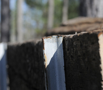 Closeup of the top edge of the backstop. The tops of the T-posts are level with the tops of the crossties.