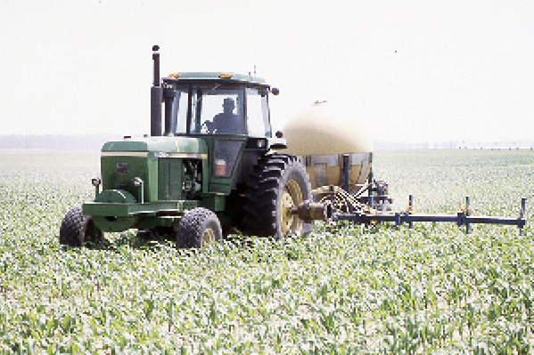 A tractor pulling a fertilizer container over crops.
