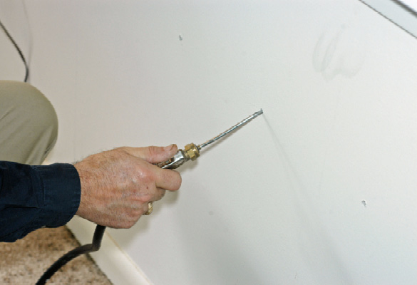 A person's hand with a long, narrow tool inserted into a sheetrock wall.