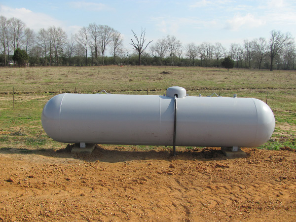A propane tank anchored on the ground in front of a field.