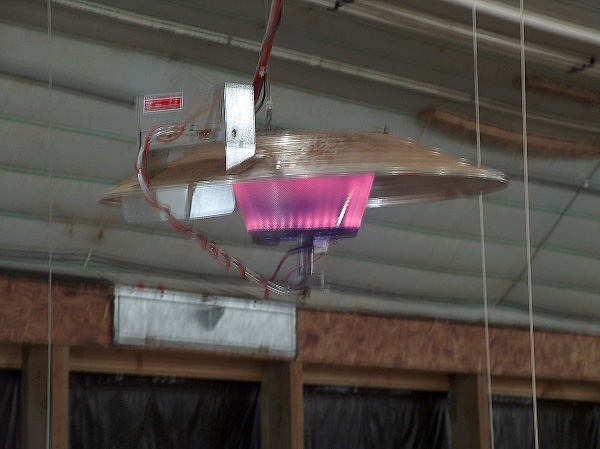 An infrared brooder hangs on wiring from the roof of a broiler house.