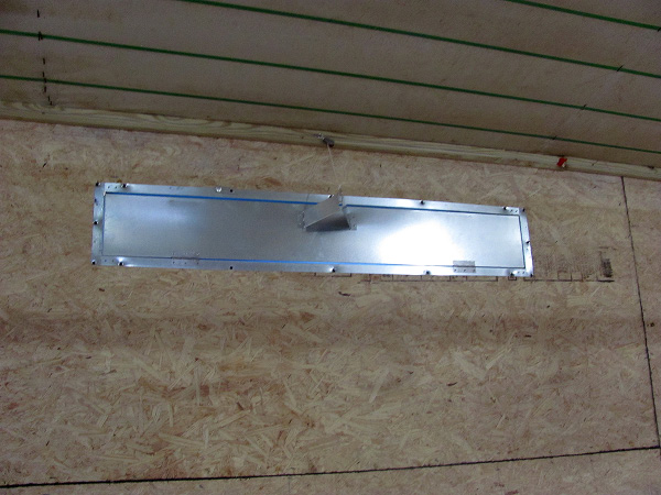A metal plate secured to the broiler house wall with a metal flap open.