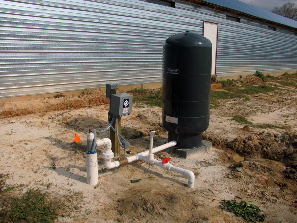 A well water pump in front of a metal-sided building.