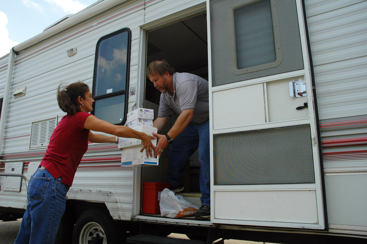 2 people loading supplies in a camper.