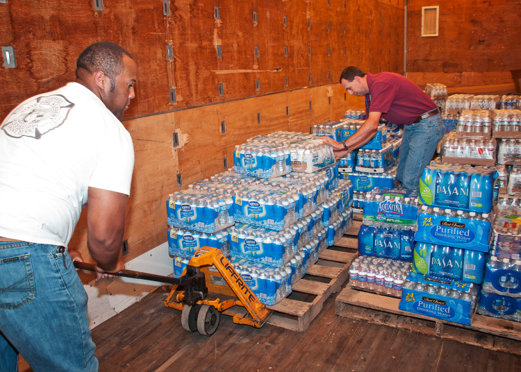 2 people loading supplies in a truck.