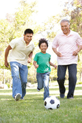 A grandfather, father, and young son play soccer together in a park.