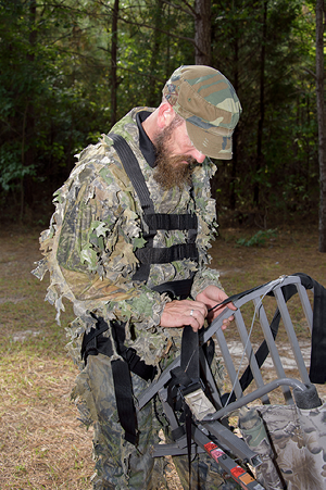 A man inspecting his tree stand equipment. The man has the full-body harness on.