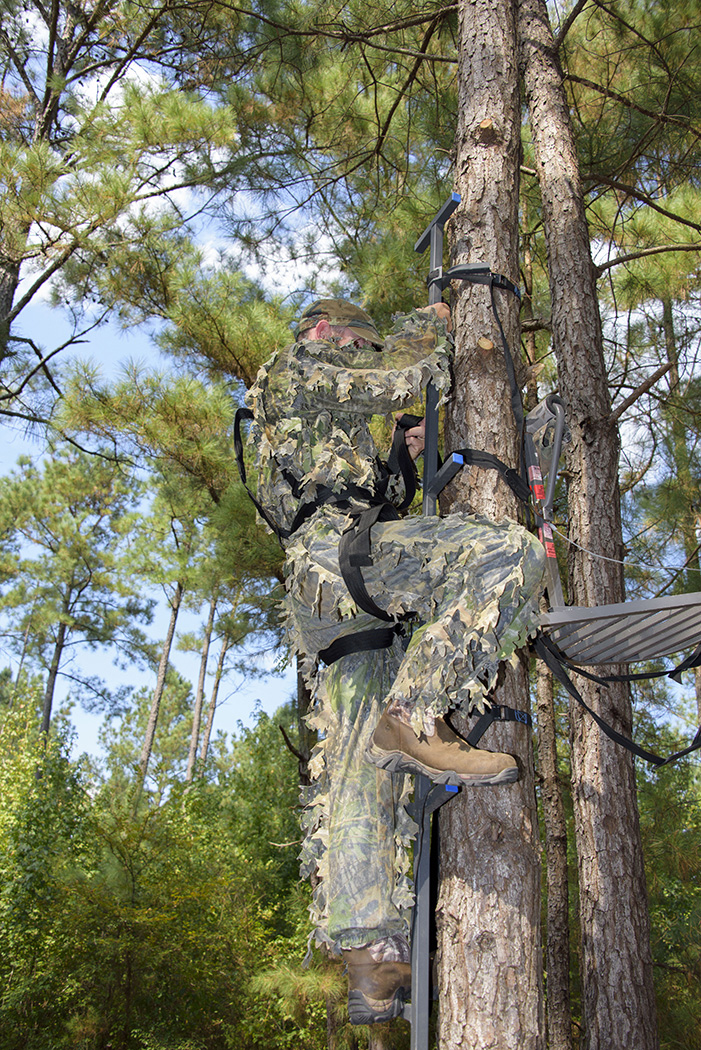 A hunter climbs a tree with his hunting stand.