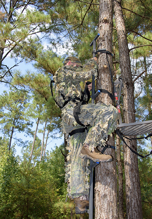A man starting to climb into the tree stand. He is at the base and using the full body harness which is attached at his shoulders and legs. The harness is also strapped around the tree.