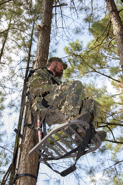 A man climbing a tree stand, off of the ground. One hand is on the stand while the other hand is on the safety strap.