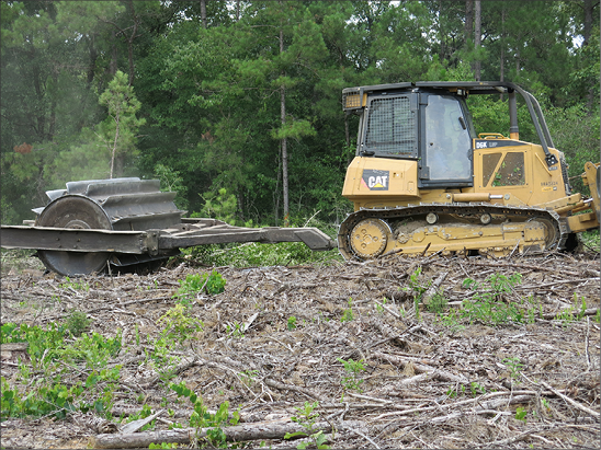 A bulldozer pulls a large, round implement over logging debris.