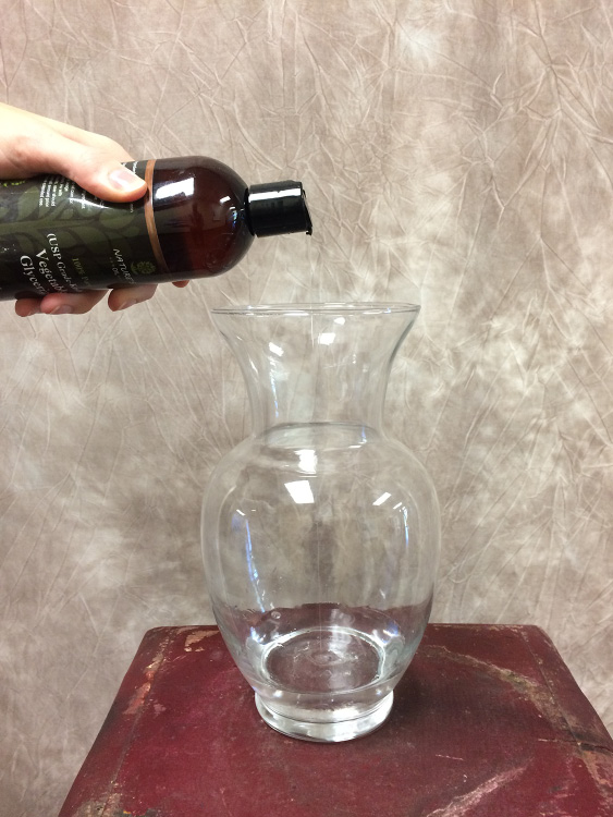 Bottle of glycerin pourin contents into glass vase.
