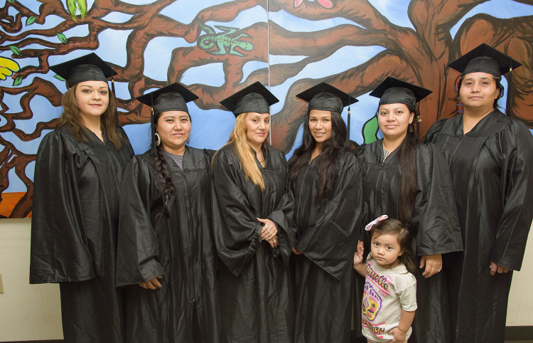 A group of Hispanic graduates in caps and gowns.