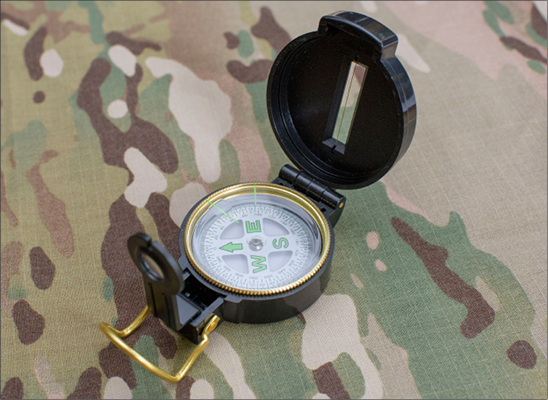 An open compass on a camouflage background.