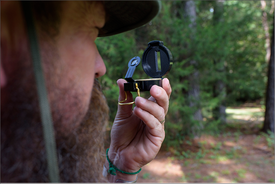 A person holds a compass up and peers through it at an object in the distance.