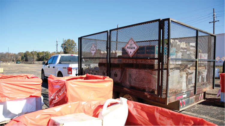 "A pickup truck with a large, enclosed trailer sits at a collection location. The trailer has hazard placard with the word ""POISON."""